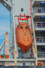 orange life boat docked to a large tanker
