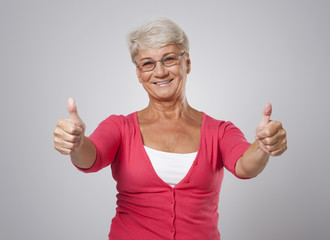Successful senior woman with thumb up