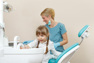 Happy little girl at the dentist takes water