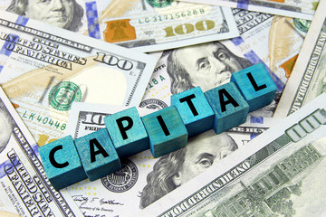 word capital on wooden cubes on american dollars background
