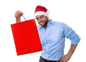 handsome man in santa hat holding red shopping bag