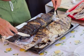 Man preparing grilled fish for dinner using silverware