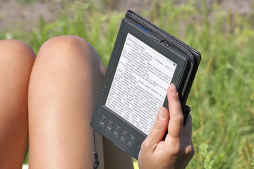 woman reading e-book outdoor