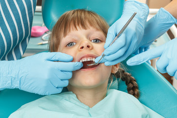 Close-up of little girl having her teeth checked by dentist