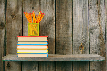 Books and pencils on a wooden shelf.