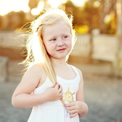 Portrait of a smiling little girl with a golden hair outdoors .