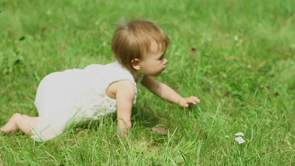 Baby girl crawling on a green grass, slow motion