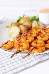 Prawns dish with potatoes and sauce with glass