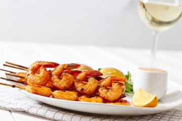 Prawns dish with potatoes and sauce with glass of wine