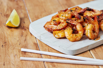 Shrimps on a wooden board with chopsticks