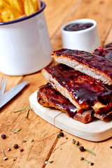 Barbecue ribs on vintage wooden table and sauce