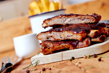 Barbecue ribs on vintage wooden table with french fries