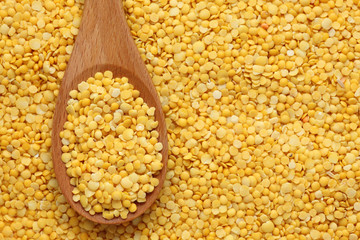 Yellow lentils in a wooden spoon