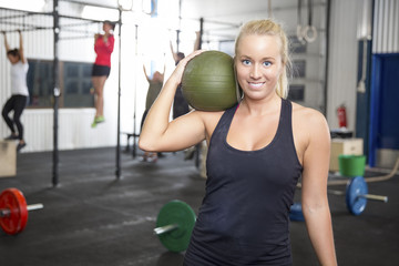 Smiling blonde woman with slam ball at fitness gym
