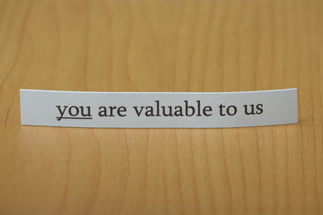 You are valuable to us typed on a strip of paper