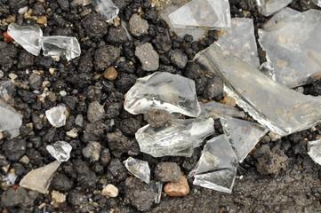 pieces of broken glass on wet asphalt