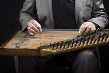 Classic musician playing kanun over black background
