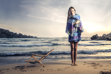 beautiful woman on the beach trying cold