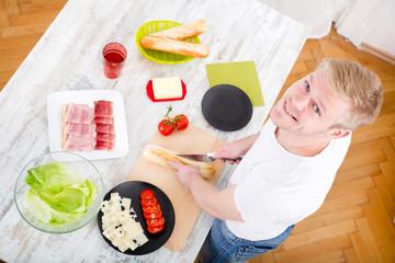 Junger Mann bereitet ein Sandwich zu
