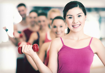 group of smiling people with dumbbells in the gym