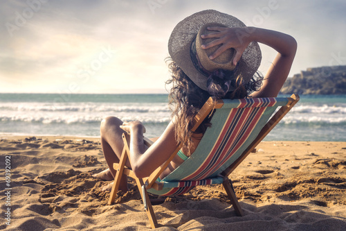 canvas print picture young woman who is taking the sun on the beach