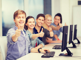 students with computer monitor showing thumbs up