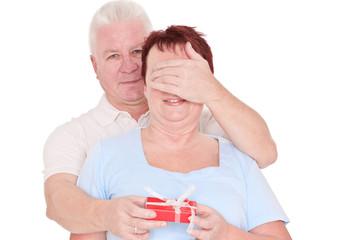 senior man gives gift to woman