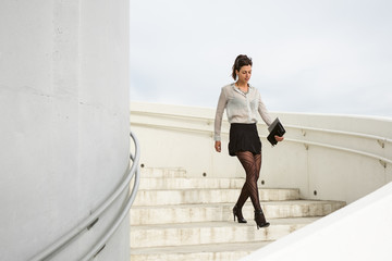 Trendy modern businesswoman walking down stairs