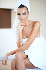 Woman Wearing White Bath Towel with Hand on Chin