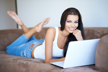 Woman smiling as she relaxes with her laptop