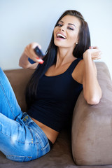 Beautiful woman laughing at the television