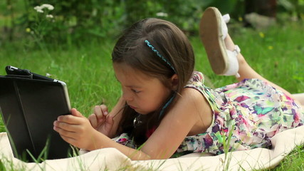 Little girl lying on grass and playing tablet pc