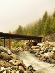 Wooden bridge over Alps rapids on quick mountain torrent in Alps