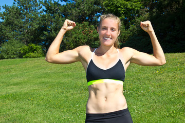 Fit, athletic woman flexing her muscles