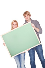 young happy couple holding a blackboard