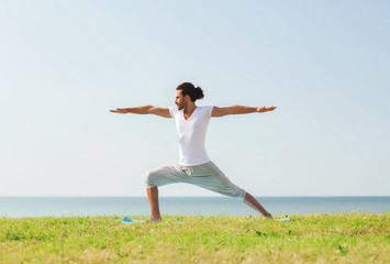smiling man making yoga exercises outdoors