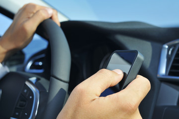man using a smartphone while driving a car