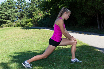 Fit woman stretching her muscles before running