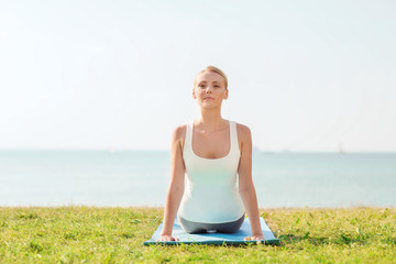 young woman making yoga exercises outdoors