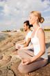 smiling couple making yoga exercises outdoors
