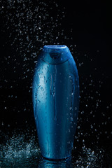 shampoo bottle in falling drops of water