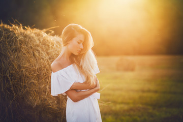Beautiful blond in field at sunset