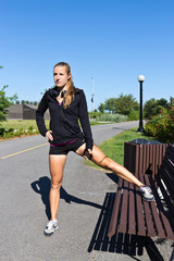 Woman stretching along a jogging trail