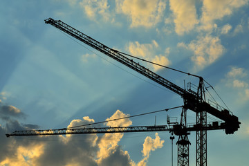 Construction cranes against of the sun