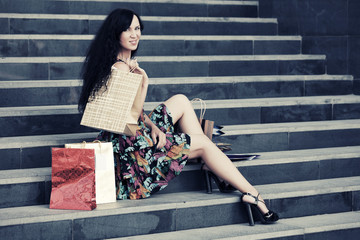 Happy young fashion woman with shopping bags on the mall steps