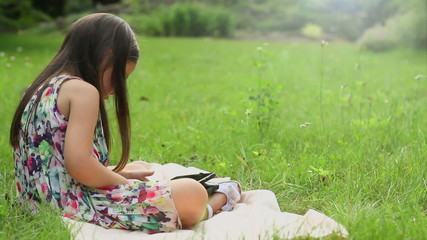 Little girl sitting on grass and playing tablet pc