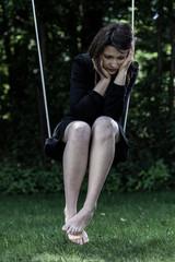 Worried woman sitting on swing