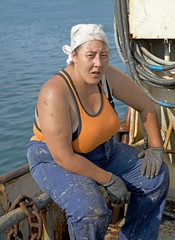 Woman painter removes old paint on a fishing seiner