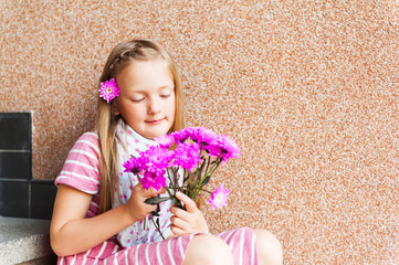 Kid girl with pink flowers, close up portrait