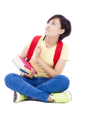 young student girl sitting on floor with book and thinking